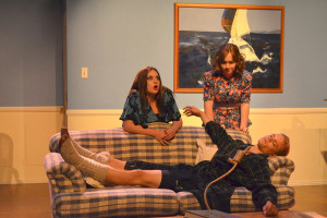 Fluff(left, Madeline Blomdahl) and Margaret Aimes(right, Alison Galvin) are shocked to find Morton Pitkit(Nick Welter) dead on the couch.