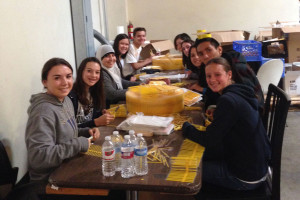 NHS members Daria Lasc, Kelsey Hampson, Ayah Kantari (left side-front to back), Katelyn Lowry, and Angel Menchaca (right side-front to back) helped cut and package straws at the Second Harvest Food Bank.