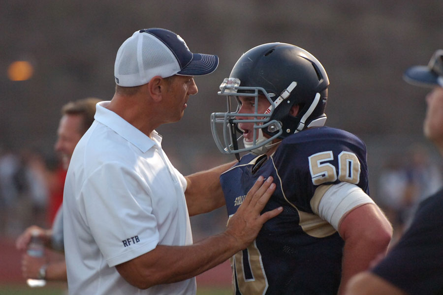 Coach Iavarone gives wide receiver Austin Cook (12) a pre-game pep talk before the first home game against Canyon High School. This is Cook's final season playing football at SJHHS and he is looking forward to what the season has in store.