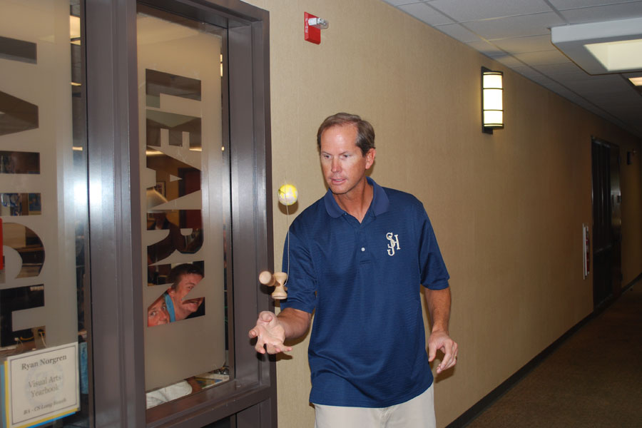Mr. Norgren concentrates on playing with a kendama outside of his classroom.