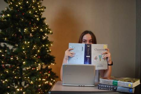 GETTING PUNCHED BY AP CLASSES: Maria Gasch (12), studies by the Christmas tree, looks at her AP Chemistry book, and wonders where her vacation has gone. Most people associate the break with chances to hang out with loved ones and no school. The reality is that her break is filled with schoolwork causing her to have a small amount of time to spend with family and friends. Photo by Maggie Barnes