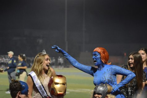 Mrs. Klingbeil, Sophomore and Senior English teacher, portrays super villain Mystique in this year's Halftime Show and pretends to snatch Queen Brittany Hill's (12) crown.  Her makeup was done by Celina Gigliello (12) of the Drama department.