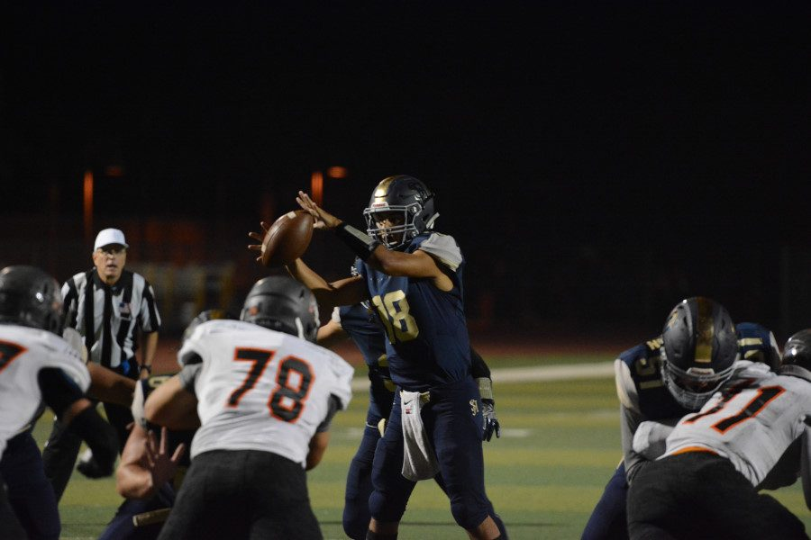 QB Matt Rodriguez (12) attempts to complete a play called by Coach Flowers, SJHHS's coach for the past 5 years.