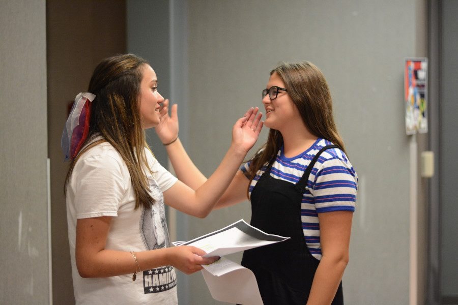 Anabelle Rigg (11) and Sydney Young (10) act out a line from Dark of the Moon in the hallways surrounding their class. The story takes place in the Appalachian countryside where conflict between humans and witches ensues. Photo by Nate Giraud