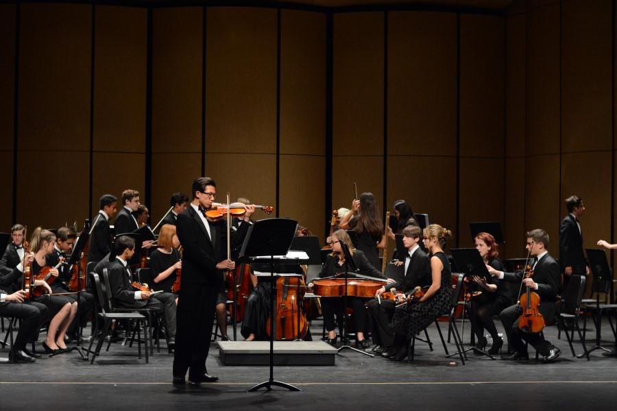 Orchestra student Declan Hayworth plays a soloist song while orchestra students ready themselves to play. Photo by Rebekah Sterns