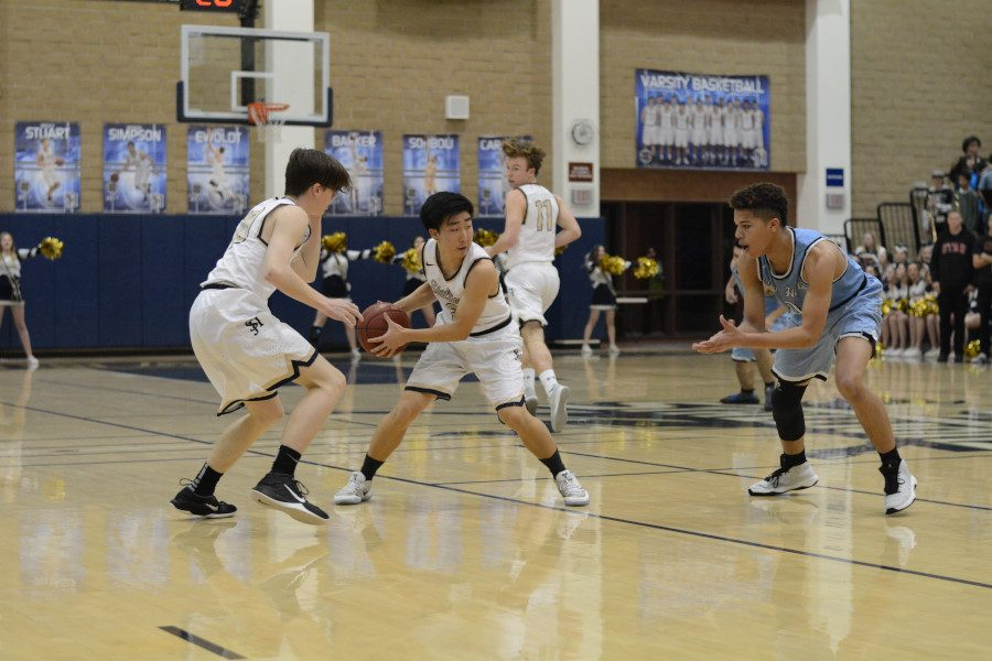 Aaron Shin secures the ball and stares down the defender during the 1st quarter of a 61-50 win over Dana Hills on Senior Night.