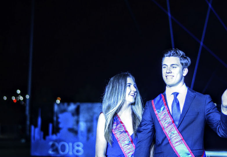 Julia Minier and Jared Brawner smile as they are introduced to the crowd during the halftime show at the homecoming football game. The couple was later crowned homecoming king and queen for their senior year.