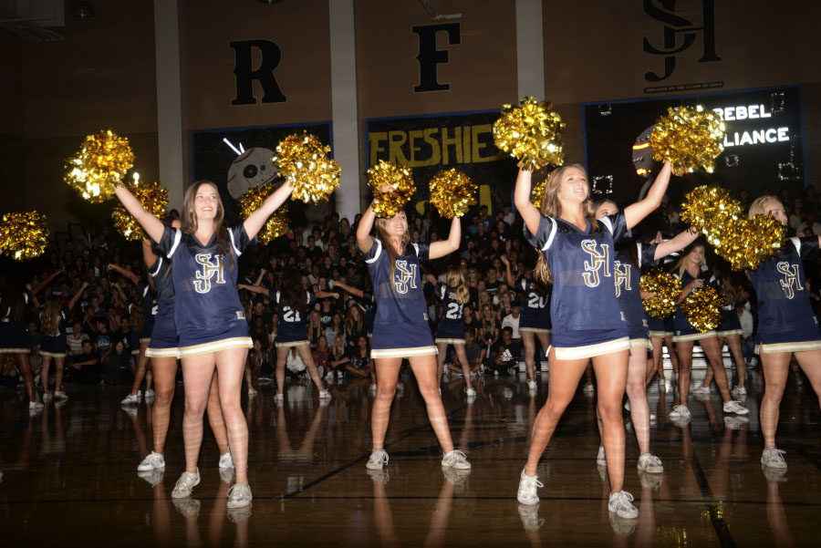 The varsity cheerleaders motivate and encourage the crowd to cheer along at the Homecoming Pep Rally.