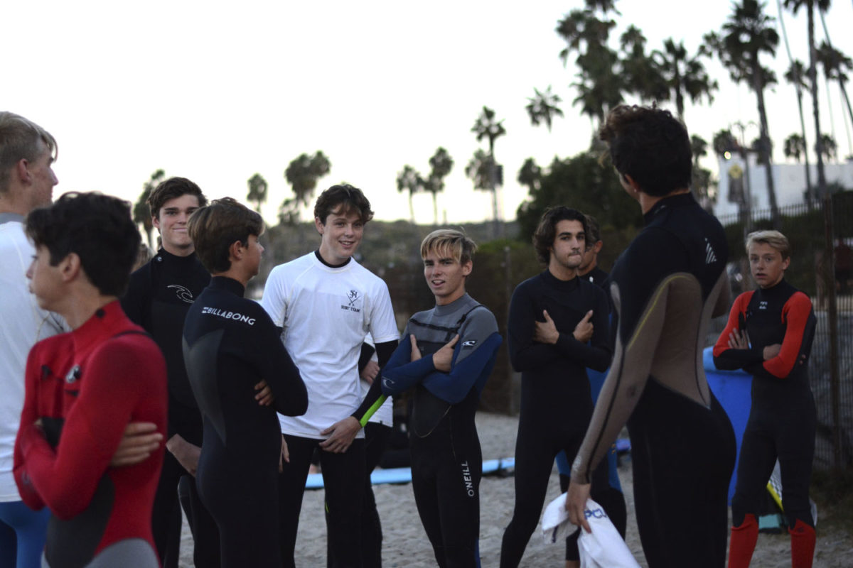 Members of the Surf Team socializing before their pre-surf stretches at 204 beach.