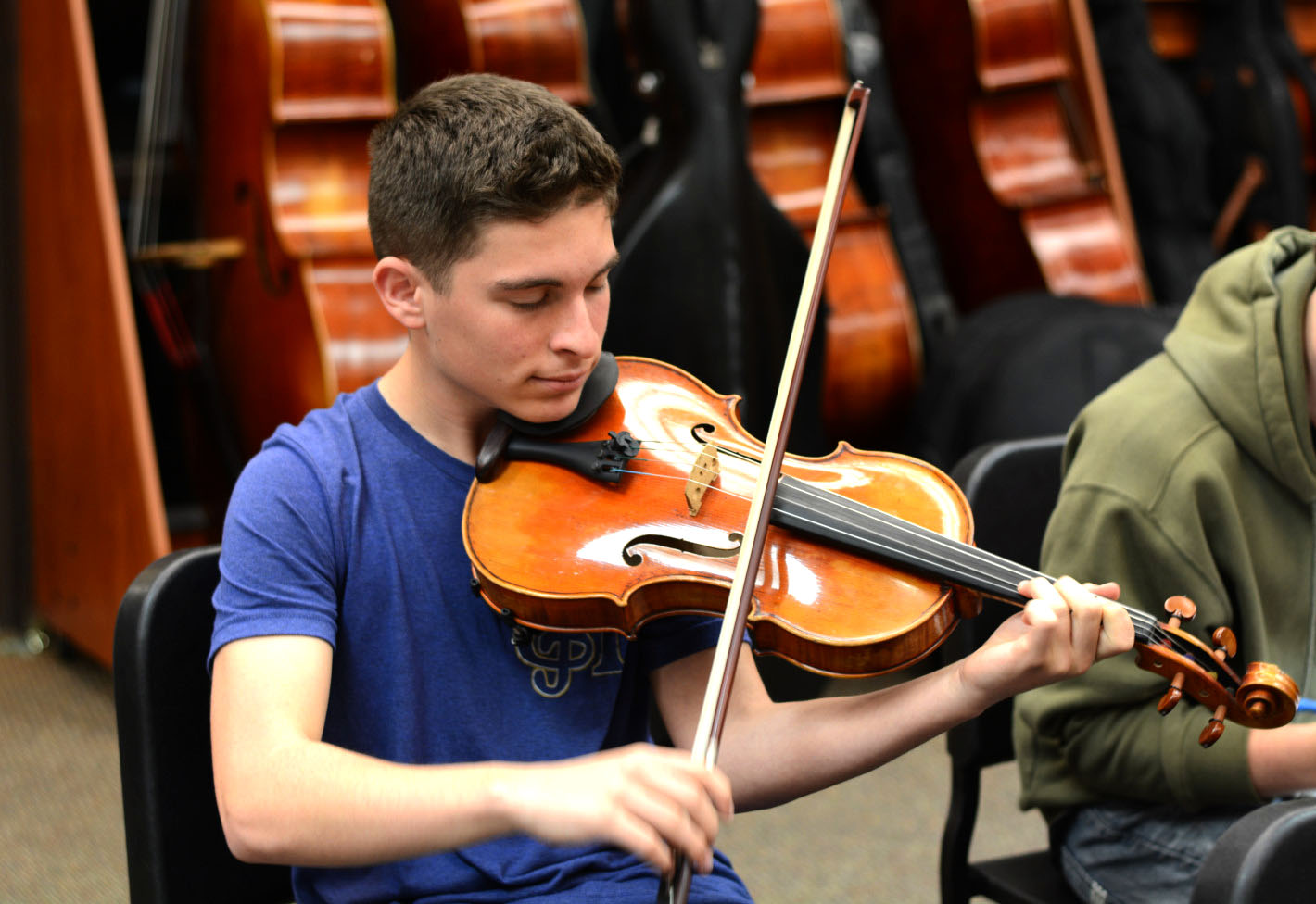 Cayden Walters (12) plays his viola in the  instrumental music room during orchestra rehearsal. He is the section leader of the section and is rehearsing  John Williams'
