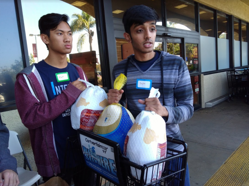 Juniors+Jaylan+Patel+and+Matt+Fong+hold+three+frozen+turkeys+outside+a+local+grocery+store.+The+boys%2C+along+with+junior+Brandon+Tong%2C+were+invited+to+go+in+the+store+and+fill+two+carts+with+donations%2C+after+a+stranger+offered+to+pay+for+everything.+The+club+ended+up+collecting+enough+food+to+feed+100+families.+It+donated+to+underprivileged+families+in+San+Juan+Capistrano+and+to+the+families+of+deployed+Marines+who+live+on+the+Camp+Pendleton+base.+