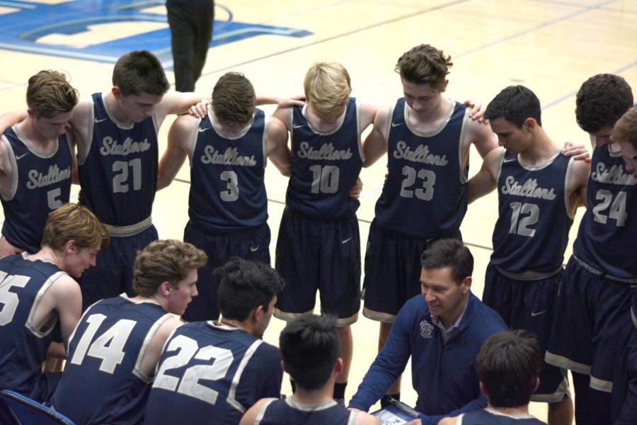 The+boys%27+Varsity+basketball+team+huddles+before+their+game+against+Dana+Hills.+The+Stallions+won+49-45.