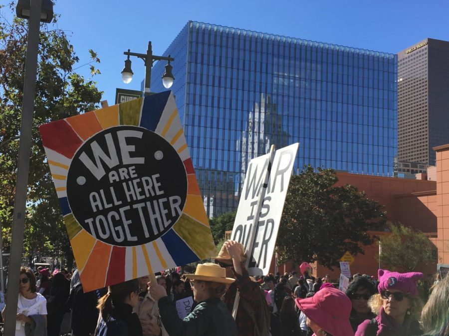 Women carry signs expressing unity as they march through Los Angeles for the 2018 Womens March