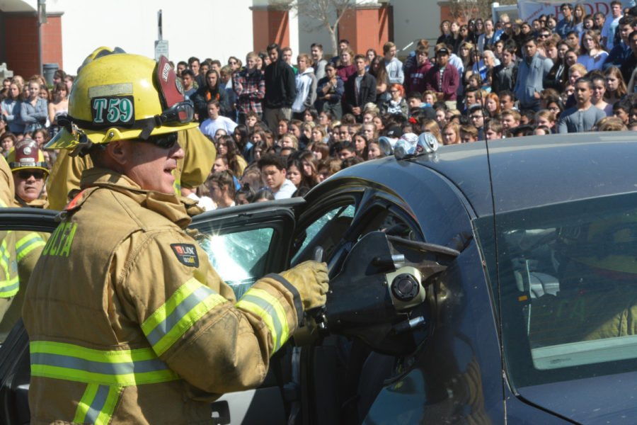 A firefighter uses the jaws of life in order to free Stephen Margaretis (11)  from the crashed car in the Every 15 Minutes mock crash program at SJHHS.