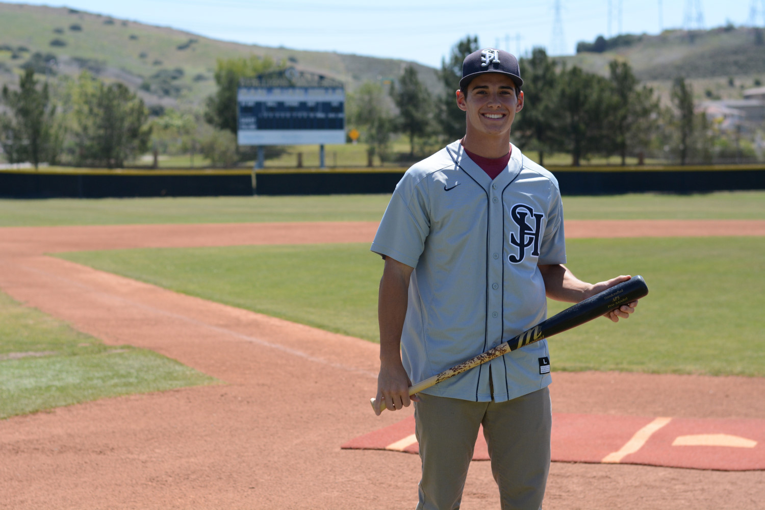 Liam O'Connor stands in the SJHHS baseball field while wearing his Stallion baseball uniform.