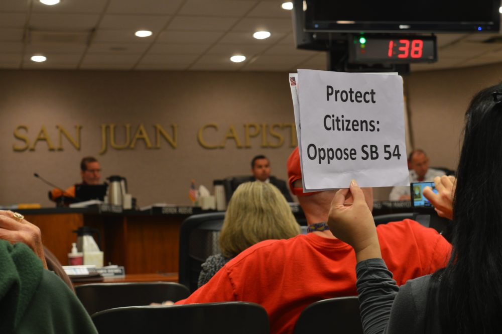 A supporter of the symbolic resolution against Senate Bill 54, this woman holds a sign showing her disagreement with the bill. The city council in the distance, listening to the public and what they have to say.