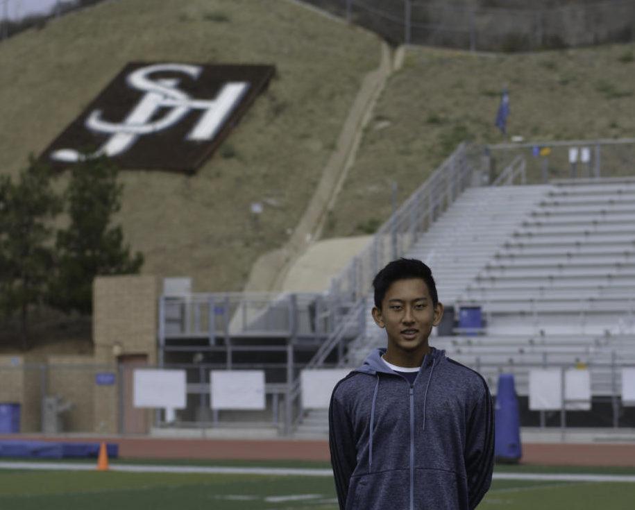 Tony Wang, freshman varsity kicker, stands in The Badlands stadium at SJHHS.