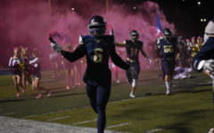 Darius Jackson, 6, carries a smoke bomb during the last home football game against Aliso Niguel High School.