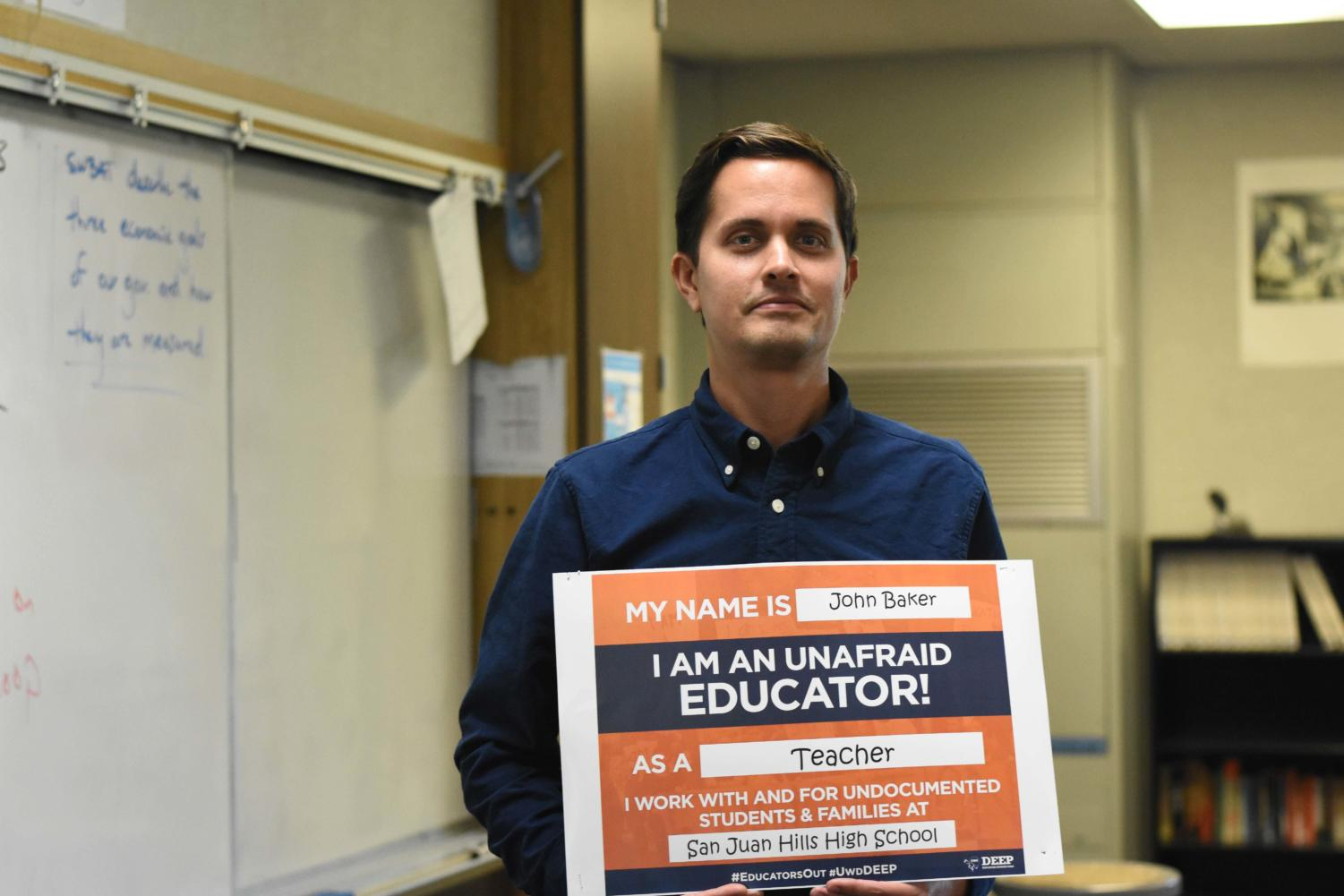 History tecaher, John Baker, holds one of the many posters that are all around teacher's rooms at SJHHS. By stating that the teachers are unafraid to educate undocumented students, it is a hope that DACA recipients will feel comfortable and accepted at SJHHS.