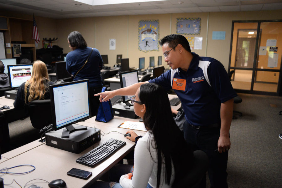 Daniel Tourn, an MPA Outreach and Recruitment Counselor from CSUF, assists students with their online college applications.