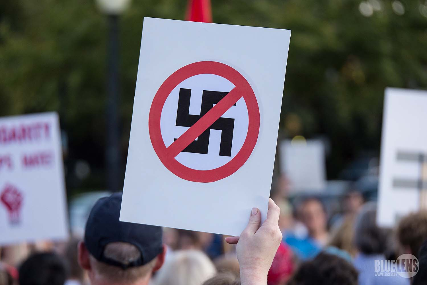 White supremacists and neo-nazis gather in Charlottesville, Virginia, for the Unite the Right rally, holding anti-semitic posters, while counter-protesters hold their anti-racism signs.