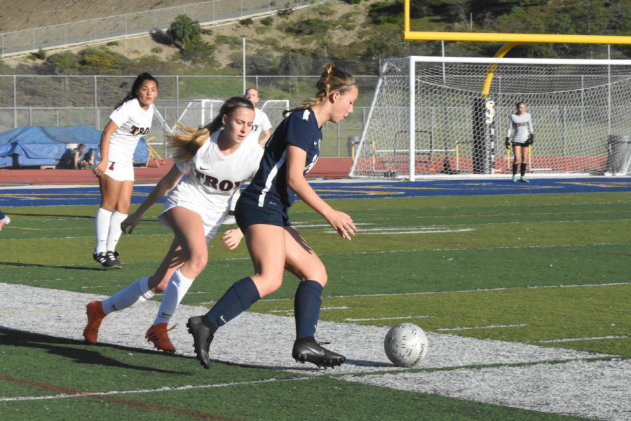 Abby Hazen (12) attempts to keep control of the ball to pass it off to her teammate in the girls' round two CIF game. SJHHS girls varsity soccer would take the win in the end with a score of 1-0.