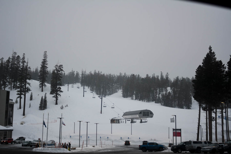 Snow falls on the slopes of Mammoth Mountain as snowboarders and skiers make their way down the mountain.