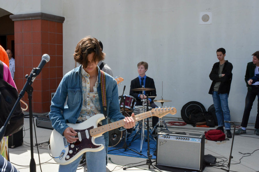 Lead guitarist of Antebellum, Jeremy Mitaux, plays along with the band's drummer, Sam Cowen, as the crowd gathers in the quad at Battle of the Bands.