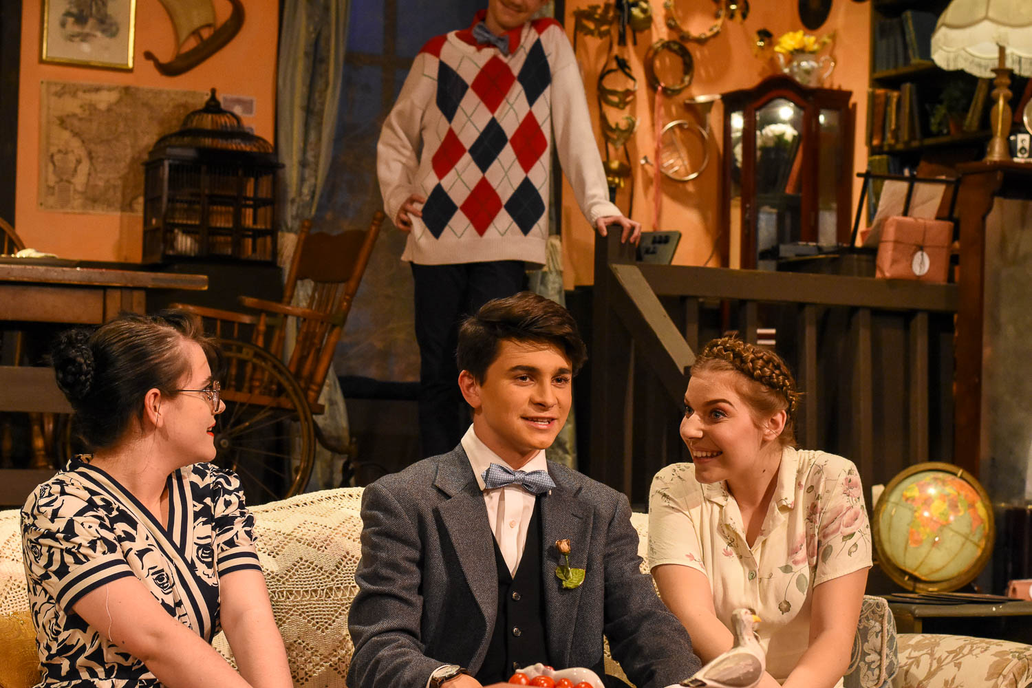 In this scene from You Can't Take it With You, Tony Kirby (Matthew Duplissey) meets Penny Sycamore (Allison Nicolai) and Essie Carmichael (Reagan Barclay), with Ed Carmichael (Connor Keithley) watching attentively.