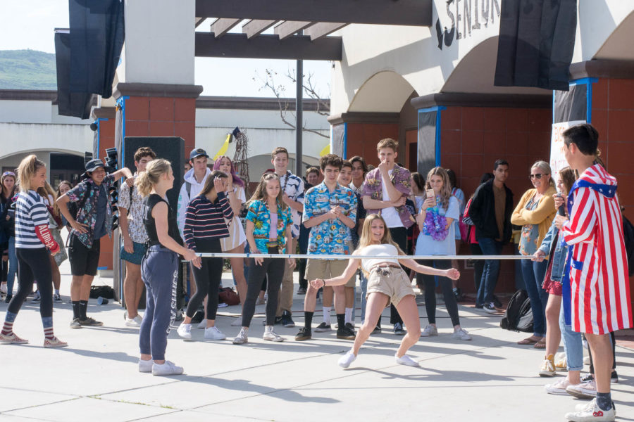 Sophomore, Brooke Scanlon competes in the limbo event for the sophomore class in Clash of the Classes Spirit Week on March 19 during break, as a crowd gathers to watch.