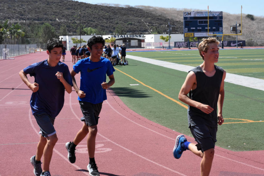 Runners for the boys cross country Freshman team, Dylan Calkins, Zach Ward, and Brandon Sotelo, begin their warm-up laps before practice.