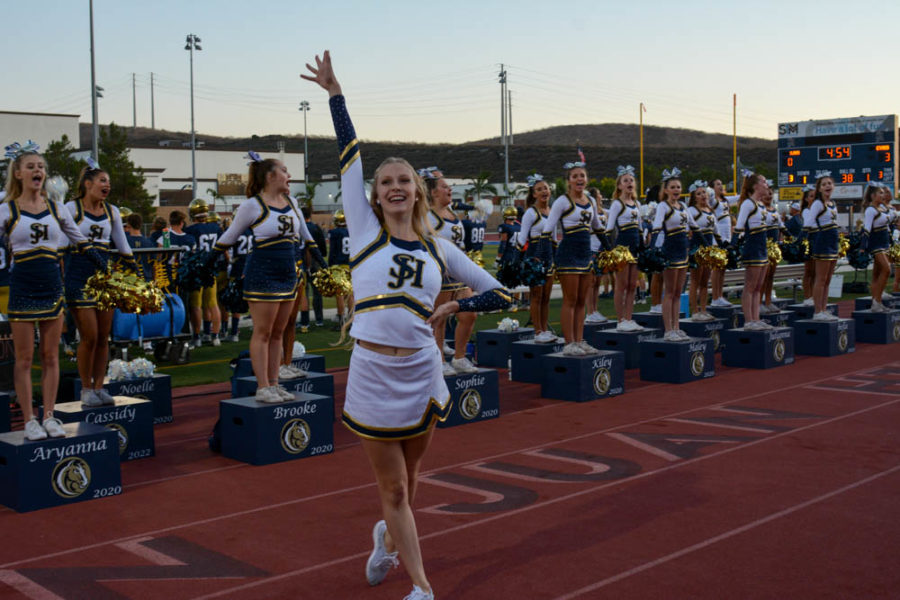 The new song team is introduced at the white out football game in the Badlands. Sarah Hansen (11) hypes up the crowd after she performed.