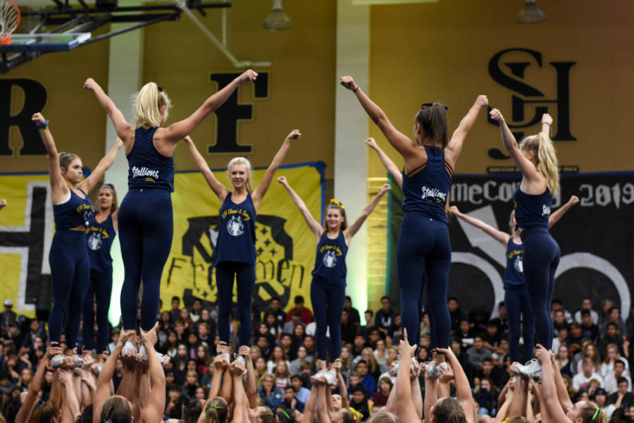 Rallied up: The pep squad holds up several flyers including Aryanna Soares (12) as they twirl in the center. The cheerleaders performed an intense routine during the pep rally.