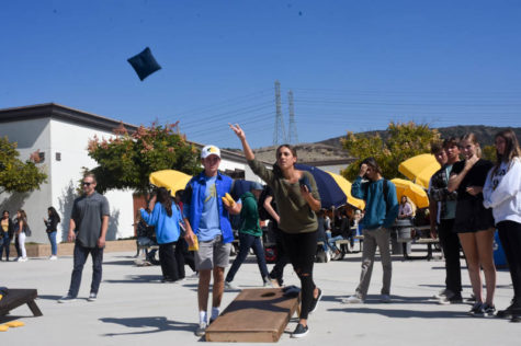 Nicole Haghani (11) throws a beanbag during her cornhole match on October 17 as her partner Luke Whittaker (11) and spectators watch. The annual cornhole tournament happened during lunch everyday this week, and teachers Matt Ahmer and Damon Garner won.