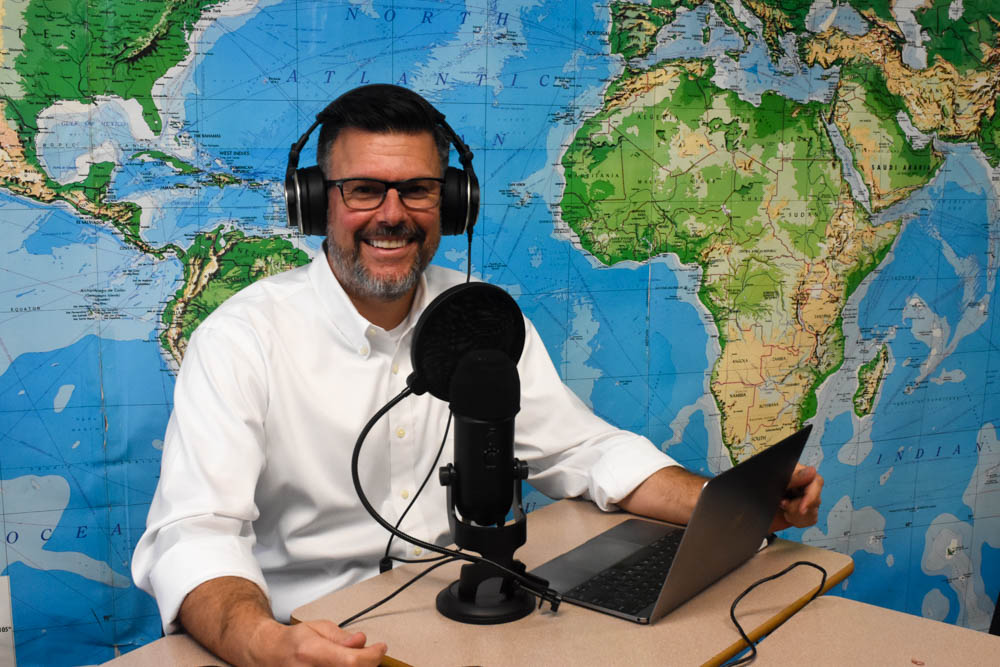 Lynde smiles as he records for his podcast, Lyndeurozone Euro Simplified. His podcast has helped hundreds of his students successfully pass their AP European History exams.