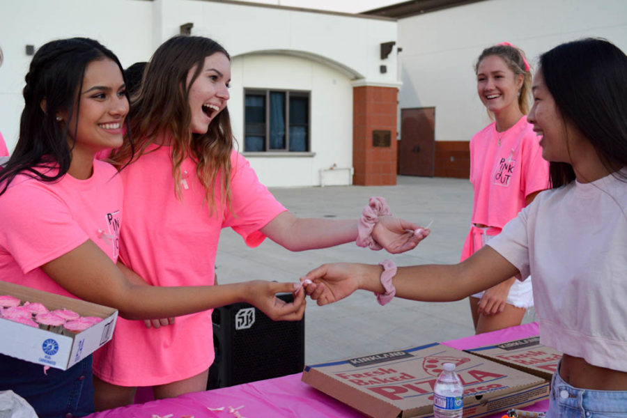 Lizzie Woods (11) and president of the Pink Ribbon Club, Siena Chacon (11) give a pink ribbon broach to Reagan Lim (11) at the tailgate before a football game. Students from the club gave food, drinks, cupcakes, and more to families in return for donations in attempts to raise money for a cure to breast cancer. The football game after the tailgate also paid tribute to breast cancer survivors and raised money for the Pink Ribbon Club.