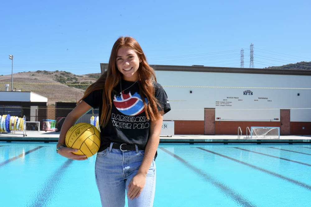 Ruby Hodge (10) stands in front of the SJHHS pool where she played last season and contributed to the Girls Water Polo League Champions title. She wears a shirt she got while playing in Barcelona, Spain for the United States national team. She is ranked within the top 14 water polo players of her age.