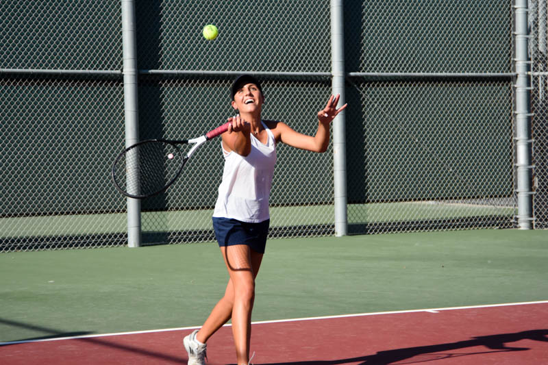 """Nicole Haghani (11), a girls tennis varsity player, slams the tennis ball across the court, while playing a match against Mission Viejo. This tennis match took place on """"Senior"""" night, a tribute to the girls senior tennis players. This was the last game of the season for the players."""