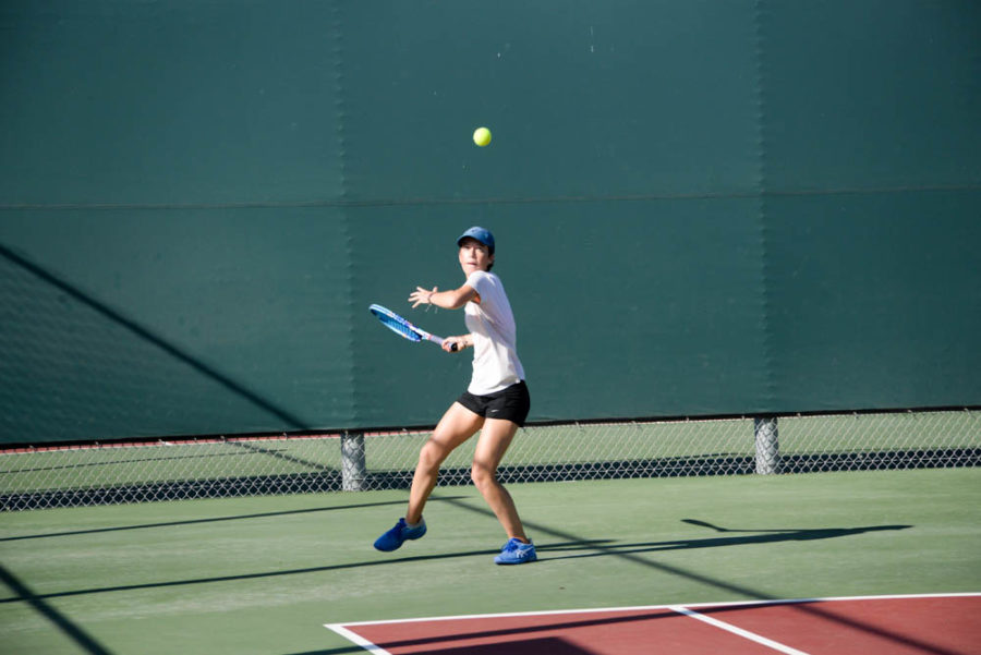 Sam Freeman (11), a girls tennis varsity player, strikes a tennis ball across the court while playing a match against Laguna Hills High School on October 17th.
