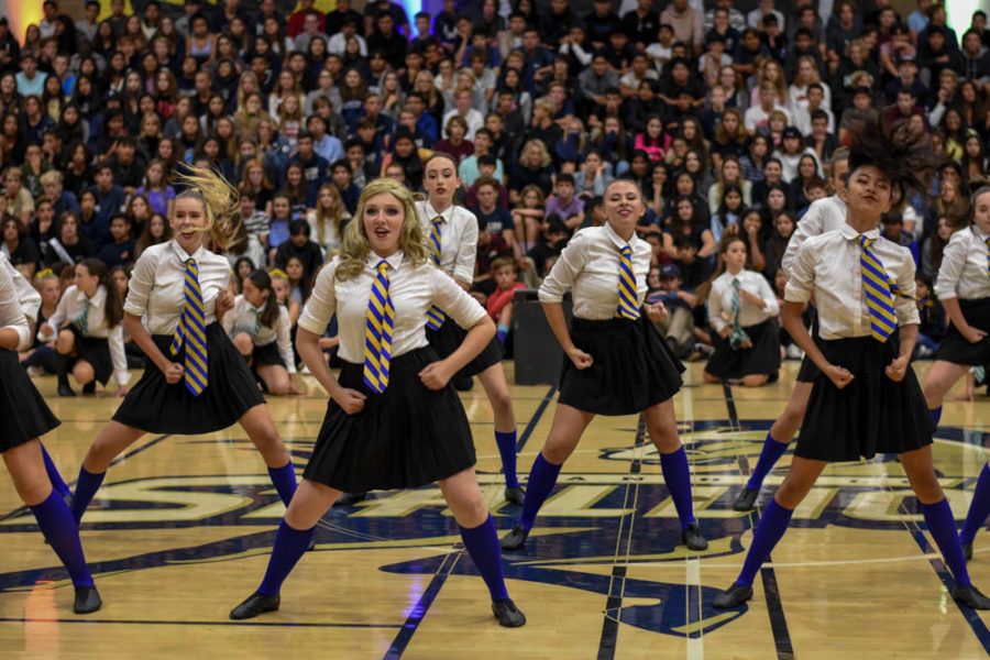 Dancers including Ashley Koclanis (10) sway their hips as they dance in the pep rally. They wear blue and yellow which symbolizes the house colors of Ravenclaw. Ravenclaw is known for being the wisdom and being the most curious of the houses in the Harry Potter series.