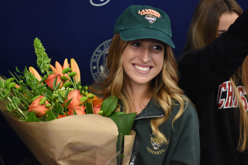 Senior+Hayden+Melin+smiles+for+her+parents+with+a+celebratory+bouquet+of+flowers+after+signing+on+for+the+Univerty+of+La+Verne%2C+where+she+will+be+playing+soccer.+