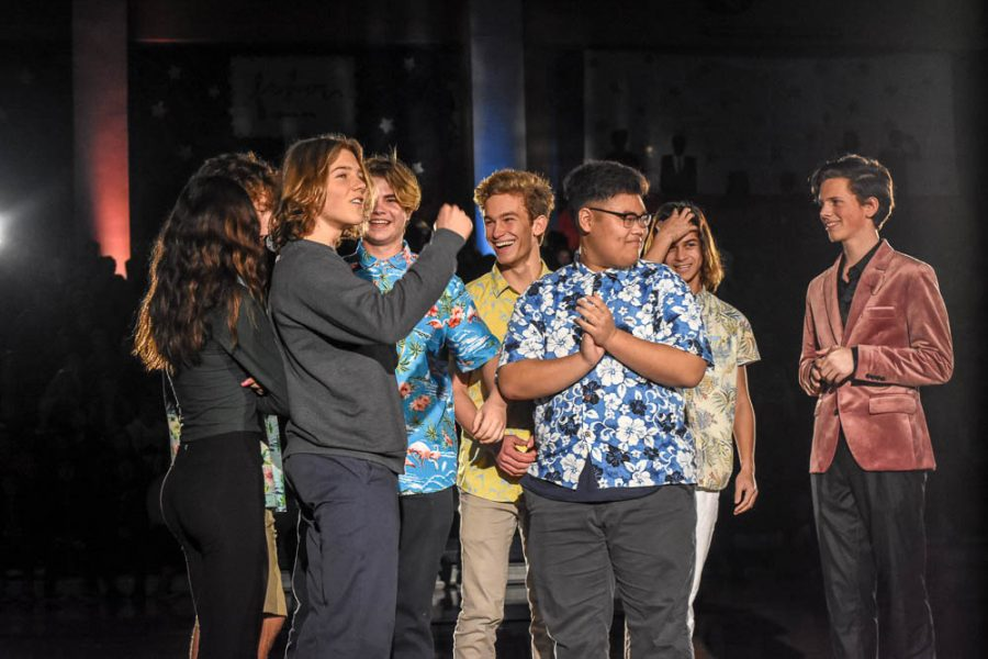 The Hawiian Band celebrates as they are announced Battle of the Bands Champions. Band members from the right: Grant Haliburton (11), Jeremy Mitaux (11), Jeremy Yu (11), Max Katz (11), Ethan Chambers (11), Sam Giraud (11), and Gianni Sirgi (11) step down in front of the crowd to be recognized for their achievement.