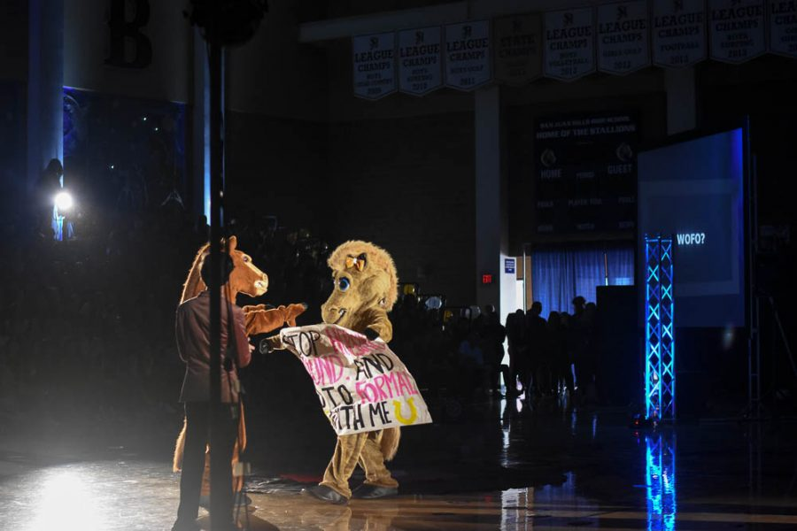 """Half way through the pep rally, Stella interrupts the scene to ask Stanley, both mascots, to Winter Formal. The sign read, """"Stop horsing around and go to formal with me""""."""