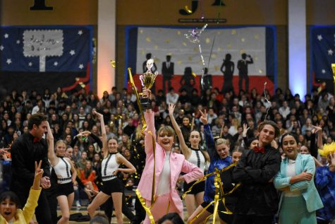 Noelle Hansen (12) acts as Taylor Swift as she wins a Grammy in the winter formal pep rally. Alina Apostolache (12) and Dylan Curialle (12) pose behind her.