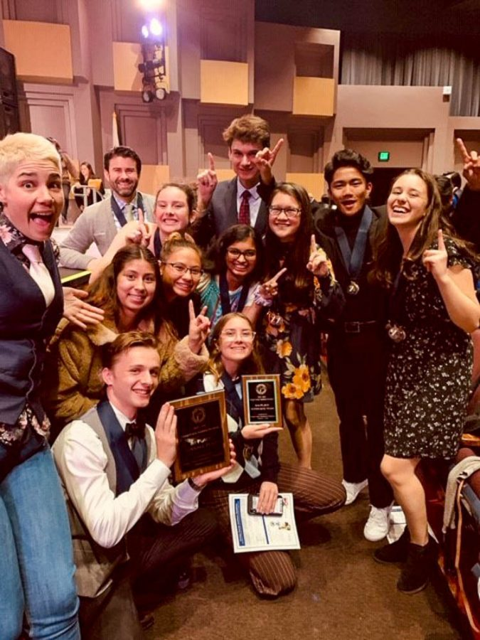 The SJHHS Academic Decathlon team stands on the stage at the Orange County Academic Decathlon Awards Ceremony for winning First Place in their division during the Overall Team Awards section of the ceremony. In addition to this, the team also won 25 individual medals and fourth place in their division for Super Quiz.