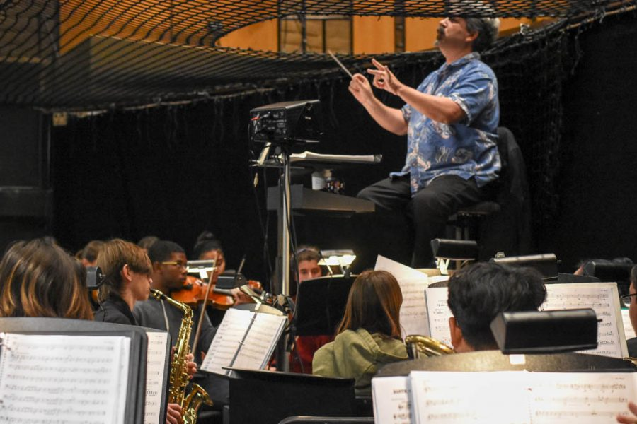 """Dean McElroy conducts the students in a song from the production during dress rehearsal. The musicians in Newsies learned around thirty songs for the show, practicing about six hours weekly. Preparation started for the show late October, and carried into February. Every instrument in band and orchestra, except the viola, was incorporated into the show, in addition to guitar and electric bass. After collaborating with the actors, the musicians said they could almost mouth the lines of the play. """"It's cool to see it all come together,"""" said musician Abraham Palmer (12)."""