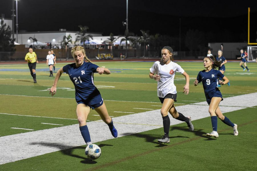Bella Mincer (12) runs the ball down the field in a non-league match against Woodbridge High School. In a close game, the Stallions won 3-1.