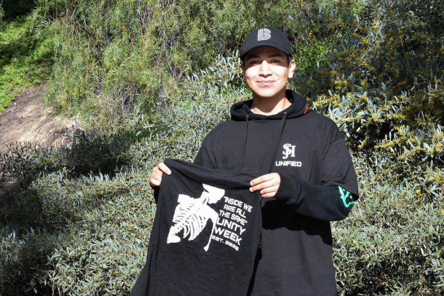 Jeffrey Tobar (12) stands with the Unity Week t-shirts. The design was made by him and other DIRHA members, and will be worn on Monday by students and faculty involved in ASB, Kindness Club, BRIDGES, and DIRHA.