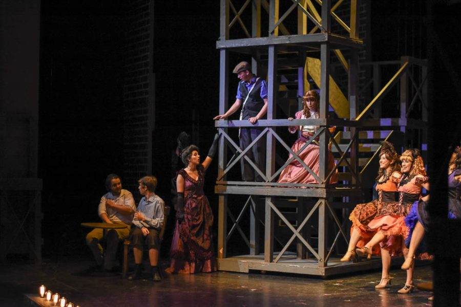 """During this number, Jack Kelly, played by Michael Liebig (11) and Katherine Plumber, played by Presley Nicholson (11) sit inside of Medda Larkin's theater. The backstage costume crew chose costumes for Jack and Katherine that would reflect the social status of each individual. For example, Jack wears a paperboy's outfit in recognition of his poverty, Katherine chooses a pink dress, demonstrating her wealth. To the right, performers dance to the song """"I Never Planned on You/Don't Come Knocking on my Door"""". On the left of Jack and Katherine, Medda Larkin, played by Madeline Halliburton, tells the two to lower their voices in her theater."""