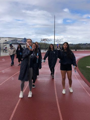 SJHHS students smile together as they walk around the track in the rain at the 2020 Walk for Wellness.